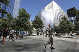 Photo - A visitor to the National September 11 Memorial and Museum takes in the sight as he walks past the museum, Friday, Sept. 6, 2013 in New York. Construction is racing ahead inside the museum as the 12th anniversary of the Sept. 11, 2001 attacks draws near. Several more large artifacts have been installed in the cavernous space below the World Trade Center memorial plaza. (AP Photo/Mary Altaffer)