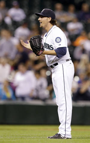Photo - Seattle Mariners relief pitcher Danny Farquhar motions toward the home umpire after being called for a balk against the Texas Rangers, allowing in a run, in the 10th inning of a baseball game Tuesday, Aug. 27, 2013, in Seattle. The Rangers won 4-3. (AP Photo/Elaine Thompson)