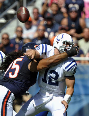 Photo -   Indianapolis Colts quarterback Andrew Luck (12) is pressured by Chicago Bears defensive tackle Matt Toeaina (75) as he releases a pass during the first half of an NFL football game in Chicago, Sunday, Sept. 9, 2012. (AP Photo/Jim Prisching)