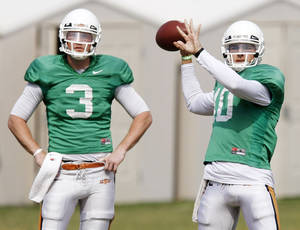 Photo - COLLEGE FOOTBALL: OSU's Clint Chelf (10) throws a pass next to Brandon Weeden (3) during spring football practice for Oklahoma State University in Stillwater, Okla., Friday, April 8, 2011. Photo by Nate Billings, The Oklahoman ORG XMIT: KOD