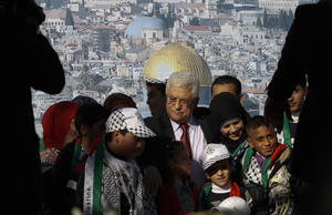 Photo - Palestinian President Mahmoud Abbas, center, is surrounded by children during celebrations for the successful bid to win U.N. statehood recognition for Palestine in the West Bank city of Ramallah, Sunday, Dec. 2, 2012. Abbas has returned home to a hero's welcome after winning a resounding endorsement for Palestinian independence at the United Nations. Israel on Sunday roundly rejected the United Nations' endorsement of an independent state of Palestine, announcing it would withhold more than $100 million collected for the Palestinian government to pay debts to Israeli companies and earlier said it would start drawing up plans to build thousands of settlement homes. (AP Photo/Nasser Shiyoukhi)