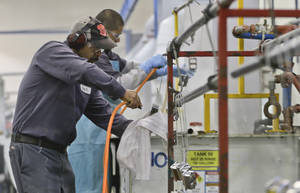 Photo - FILE - In this Thursday, Oct. 10, 2013, file photo, employees at Sheffield Platers Inc. work on the factory floor in San Diego. The labor Department releases fourth-quarter productivity data on Thursday, March, 6, 2014. (AP Photo/Lenny Ignelzi, File)