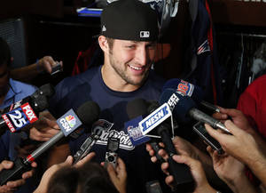 Photo - New England Patriots quarterback Tim Tebow speaks to media in the locker room after team football practice in Foxborough, Mass., Monday, Aug. 26, 2013. (AP Photo/Elise Amendola)
