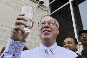 Photo - Toledo Mayor D. Michael Collins raises a glass of tap water before drinking it during a news conference in Toledo, Ohio, Monday, Aug. 4, 2014. A water ban that had hundreds of thousands of people in Ohio and Michigan scrambling for drinking water has been lifted, Collins announced Monday. (AP Photo/Paul Sancya)