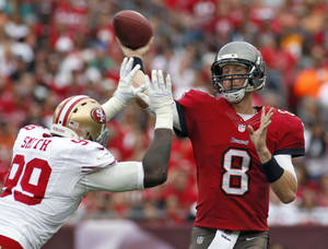 Photo - Tampa Bay Buccaneers quarterback Mike Glennon (8) fires the football as he is about to be hit by San Francisco 49ers outside linebacker Aldon Smith (99) during the third quarter of an NFL football game Sunday, Dec. 15, 2013, in Tampa, Fla. (AP Photo/Reinhold Matay)