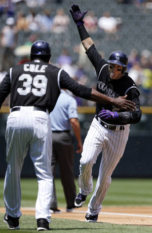 Photo - Colorado Rockies' Troy Tulowitzki (2) celebrates a solo home run with third base coach Stu Cole (39) during the first inning of a baseball game against the San Diego Padres on Wednesday, July 9, 2014, in Denver. (AP Photo/Jack Dempsey)