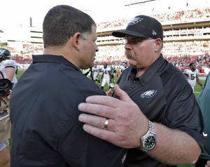 Photo - Philadelphia Eagles head coach Andy Reid, right, consols Tampa Bay Buccaneers head coach Greg Schiano after the Eagles defeated the Buccaneers 23-21 during an NFL football game Sunday, Dec. 9, 2012, in Tampa, Fla. (AP Photo/Chris O'Meara)