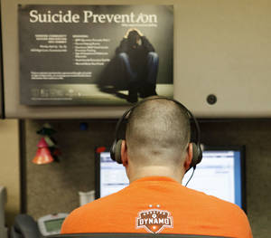 Photo - A call specialist works the phones at the Lifeline suicide prevention hotline <strong>Steve Gooch</strong>
