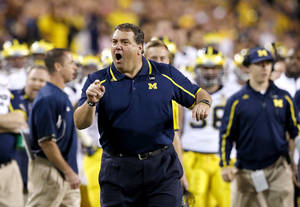 Photo - Michigan coach Brady Hoke yells at officials during the first half of the Buffalo Wild Wings Bowl NCAA college football game against Kansas State on Saturday, Dec. 28, 2013, in Tempe, Ariz. (AP Photo/Ross D. Franklin)