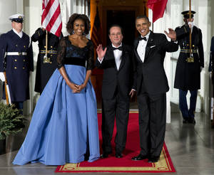 Photo - First lady Michelle Obama, left, and President Barack Obama welcome French President François Hollande for a State Dinner at the North Portico of the White House on Tuesday, Feb. 11, 2014, in Washington. (AP Photo/ Evan Vucci)