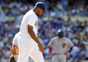 Photo - Los Angeles Dodgers relief pitcher Kenley Jansen walks back to the mound after San Francisco Giants' Hector Sanchez (not shown) hit a single to score a run in the tenth inning of a baseball game on Sunday, May 11, 2014, in Los Angeles. The Giants won 7-4 in 10 innings. (AP Photo/Alex Gallardo)