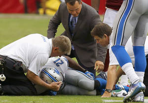 Photo - Detroit Lions' Reggie Bush (21) is attended to by training and medical staff after injuring his leg during the first half in an NFL football game against the Arizona Cardinals on Sunday, Sept. 15, 2013, in Glendale, Ariz. (AP Photo/Ross D. Franklin)