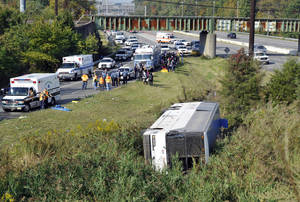 photo -   Rescue workers and passengers stand by after a bus overturned in a ditch at an exit ramp off Route 80 in Wayne, N.J. Saturday, Oct. 6, 2012. The chartered tour bus from Toronto carrying about 60 people overturned on an interstate exit ramp. Three people have been taken to hospital with non-life-threatening injuries. (AP Photo/Bill Kostroun)