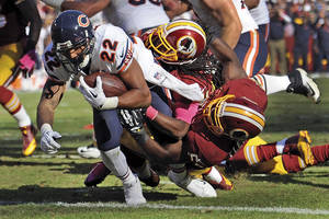 Photo - Chicago Bears running back Matt Forte (22) drags Washington Redskins strong safety Brandon Meriweather, center, and inside linebacker London Fletcher, right, into the end zone for a touchdown during the second half of a NFL football game in Landover, Md., Sunday, Oct. 20, 2013. (AP Photo/Nick Wass)