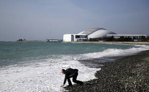 Photo - A beachgoer reaches down to touch the Black Sea as Fisht Olympic Stadium stands in the background, home of tonight's 2014 Winter Olympics closing ceremony, Sunday, Feb. 23, 2014, in Sochi, Russia. (AP Photo/David Goldman)