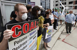 Photo -   Environmental activists carry signs and wear dust masks as they protest outside the State Corporations Commission in Richmond, Va., Tuesday, May 8, 2012. Dominion Virginia power presented its long term energy plans to state regulators. (AP Photo/Steve Helber)