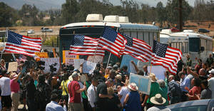 Photo - Protesters turn back three buses carrying 140 immigrants as they attempt to enter the Murrieta U.S. Border Patrol station for processing on Tuesday, July 1, 2014, in Murrieta, Calif.(AP Photo/The Press-Enterprise, David Bauman)  MAGS OUT; MANDATORY CREDIT