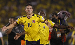 Photo - Colombia's James Rodriguez, left, and Pablo Armero celebrate at the end of a 2014 World Cup qualifying soccer match against Ecuador in Barranquilla, Colombia, Friday, Sept. 6, 2013. Colombia won 1-0. (AP Photo/Fernando Vergara)