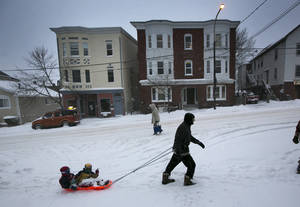 Photo - Guy McChesney pulls Lucas McChesney and Nico Doyle on a sled up Munjoy Hill during a snow storm, Friday, Feb. 8, 2013, in Portland, Maine. Snow began falling across the Northeast on Friday, ushering in what was predicted to be a huge, possibly historic blizzard and sending residents scurrying to stock up on food and gas up their cars. The storm could dump 1 to 3 feet of snow from New York City to Boston and beyond. (AP Photo/Robert F. Bukaty)