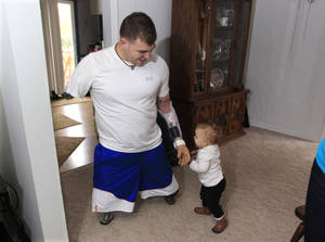 Photo -   Army Staff Sgt. Travis Mills plays with his daughter Chloe in his boyhood home in Vassar, Mich., Thursday, Oct. 4, 2012. Mills is visiting his hometown for the first time since losing all four limbs while fighting in Afghanistan. Mills, his wife, Kelsey, and their 1-year-old daughter, Chloe, will be the grand marshals of Vassar High School's homecoming parade on Thursday evening. (AP Photo/Carlos Osorio)