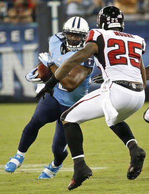 Photo - Tennessee Titans running back Shonn Greene (23) works against Atlanta Falcons strong safety William Moore (25) during the first half of an NFL preseason football game, Saturday, Aug. 24, 2013, in Nashville, Tenn. (AP Photo/John Russell)