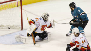 Photo - San Jose Sharks' Joe Pavelski, right, scores a goal past Calgary Flames goalie Karri Ramo during the second period of an NHL hockey game, Monday, Jan. 20, 2014 in San Jose, Calif.  (AP Photo/George Nikitin)