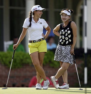 Photo - Lucy Li, right, laughs with playing partner Jessica Wallace, left, before finishing their round during the second round of the U.S. Women's Open golf tournament in Pinehurst, N.C., Friday, June 20, 2014. (AP Photo/Bob Leverone)