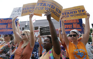 Photo - File - In this July 9, 2013 file photo, opponents and supporters of an abortion bill hold signs near a news conference outside the Texas Capitol, in Austin, Texas. New abortion restrictions passed by the Texas Legislature are unconstitutional and will not take effect as scheduled on Tuesday, a federal judge has ruled. (AP Photo/Eric Gay, File)