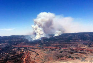 Photo - This image provided by Inci Web shows a plume of smoke in the Chuska Mountains near Naschitti, N.M. on Sunday, June 15, 2014.  Residents of a Navajo community near the New Mexico-Arizona border prepared for evacuations Monday as strong winds fanned the flames of a wildfire burning in the Chuska Mountains.  Fire officials were conducting reconnaissance missions to get a better handle on the fire's size, but Navajo Nation officials said more than 3 square miles have been charred since the fire was first reported Friday. (AP Photo/Inciweb)