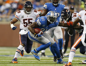 Photo - Chicago Bears cornerback Charles Tillman (33) and outside linebacker Lance Briggs (55) close in on Detroit Lions wide receiver Calvin Johnson (81) during the first quarter of an NFL football game at Ford Field in Detroit, Sunday, Sept. 29, 2013. (AP Photo/Paul Sancya)