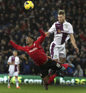 Photo - Aston Villa's Nathan Baker, right,  heads the ball from Cardiff City's Fraizer Campbell during their English  Premier League match at the Cardiff City Stadium, Cardiff  Tuesday Feb. 11, 2014. (AP Photo/Nick Potts/PA) UNITED KINGDOM OUT
