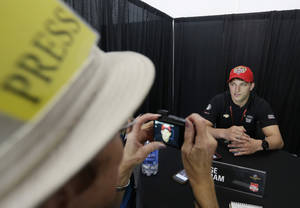 Photo - Sage Karam has his photo taken by Lynne Huntting as he responds to a question during a media interview for the Indianapolis 500 IndyCar auto race at the Indianapolis Motor Speedway in Indianapolis, Thursday, May 22, 2014. (AP Photo/Darron Cummings)