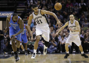 Photo - San Antonio Spurs' Tim Duncan (21) steals the ball from Oklahoma City Thunder's Kendrick Perkins (5) during the first half of an NBA basketball game, Wednesday, Jan. 22, 2014, in San Antonio. (AP Photo/Eric Gay)