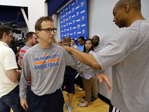 Photo -                    Coach Scott Brooks exchanges greetings with Caron Butler on Friday during media access after Thunder practice in Oklahoma City. In Thursday's NBA Playoffs Game 6 against the Grizzlies, Brooks swapped Thabo Sefolosha for Butler in the game's starting lineup.                     Photo by Steve Sisney, The Oklahoman