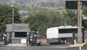 Photo - A bus carrying children arrives to a border patrol facility in Nogales, Ariz., Saturday, June 7, 2014. Arizona officials said that they are rushing federal supplies to a makeshift holding center in the southern part of the state that's housing hundreds of migrant children and is running low on the basics. (AP Photo/The Arizona Republic, Patrick Breen)  MARICOPA COUNTY OUT; MAGS OUT; NO SALES