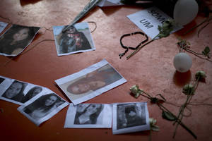 photo - A makeshift memorial that include pictures of the victims of the Kiss nightclub fatal fire is seen inside the gymnasium where a collective funeral was held a day earlier, in Santa Maria, Brazil, Tuesday, Jan. 29, 2013. A fast-moving fire roared through the crowded, windowless nightclub, early Sunday, killing more than 230 people.  The first funeral services were held Monday for the victims. Most of the dead were college students 18 to 21 years old, but they also included some minors. Almost all died from smoke inhalation. (AP Photo/Felipe Dana)
