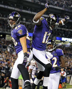 Photo -   Baltimore Ravens tight end Dennis Pitta, left, celebrates his touchdown with teammates Jacoby Jones (12) and Torrey Smith, back, in the first half of an NFL football game against the New England Patriots in Baltimore, Sunday, Sept. 23, 2012. (AP Photo/Nick Wass)