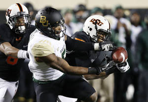 Photo - Oklahoma State linebacker Joe Mitchell (29) breaks up a pass intended for Baylor wide receiver Antwan Goodley (5) in the fourth quarter of an NCAA college football game in Stillwater, Okla., Saturday, Nov. 23, 2013. Oklahoma State won 49-17. (AP Photo/Sue Ogrocki)