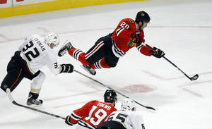 photo - Chicago Blackhawks left wing Brandon Saad (20) shoots and scores past Anaheim Ducks defenseman Toni Lydman (32), of Finland, as Blackhawks' Jonathan Toews (19) and Ducks' Emerson Etem watch during the second period of an NHL hockey game, Tuesday, Feb. 12, 2013, in Chicago. (AP Photo/Charlie Arbogast)