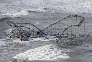 Photo -   FILE - In this Wednesday, Oct. 31, 2012 file photo, waves wash over a roller coaster from a Seaside Heights, N.J., amusement park that fell in the Atlantic Ocean during Superstorm Sandy. (AP Photo/Mike Groll, File)