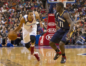 Photo - Philadelphia 76ers' Michael Carter-Williams, left, makes his move against New Orleans Pelicans' Jrue Holiday, right,  during the second quarter of an NBA basketball game Friday, Nov. 29, 2013, in Philadelphia. (AP Photo/Chris Szagola)