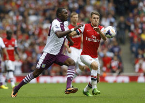 Photo - Arsenal's Aaron Ramsey, right, vies for the ball with Aston Villa's Christian Benteke during the English Premier League soccer match between Arsenal and Aston Villa at the Emirates Stadium in London, Saturday, Aug. 17, 2013. (AP Photo/Kirsty Wigglesworth)