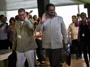 photo -   Ivan Marquez, right, and Ricardo Tellez, members of the negotiation team for Colombia&#039;s Revolutionary Armed Forces of Colombia, or FARC, wave as they arrive for peace talks in Havana, Cuba, Monday, Nov. 19, 2012. Marquez, the top FARC negotiator, announced a unilateral cease-fire on Monday, before heading into much-anticipated peace talks with his government counterparts. (AP Photo/Ramon Espinosa)  