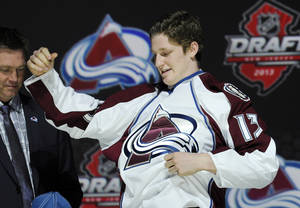 Photo - Nathan MacKinnon, a center, pulls on a Colorado Avalanche sweater after being chosen 1st overall in the first round of the NHL hockey draft, Sunday, June 30, 2013, in Newark, N.J. (AP Photo/Bill Kostroun)