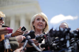"photo -   Arizona Gov. Jan Brewer speaks to reporters outside the Supreme Court in Washington, Wednesday, April 25, 2012, after the court's hearing on Arizona's ""show me your papers"" immigration law. (AP Photo/Charles Dharapak)"