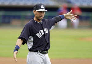 Photo - New York Yankees shortstop Derek Jeter stretches before an exhibition baseball game against the Philadelphia Phillies, Thursday, March 6, 2014, in Clearwater, Fla. (AP Photo/Charlie Neibergall)