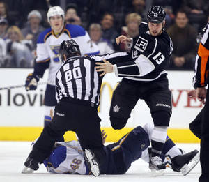 photo - Los Angeles Kings left wing Kyle Clifford (13) steps over St. Louis Blues defenseman Roman Polak (46), of the Czech Republic, after forcing Polak to the ice during a fight in the first period of an NHL hockey game Tuesday, March 5, 2013, in Los Angeles.  Linesman Thor Nelson (80) protects Polak from further injury on the ice. (AP Photo/Alex Gallardo)