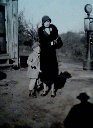 James with mother Mildred Meek Bumgarner in front of the family's store and filling station in Denver, OK.