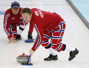 Photo - Norway's Torger Nergaard, right, sweeps ahead of a shot by skip Thomas Ulsrud during a men's curling training session the 2014 Winter Olympics, Sunday, Feb. 9, 2014, in Sochi, Russia. (AP Photo/Robert F. Bukaty)