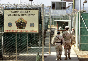 Photo - FILE - In this June 27, 2006 file photo, reviewed by a U.S. Department of Defense official, U.S. military guards walk within Camp Delta military-run prison, at the Guantanamo Bay U.S. Naval Base, Cuba. The White House is threatening that President Barack Obama would veto the defense bill unless Congress makes changes. The Office of Management and Budget issued a statement Thursday as the Senate debated the $631 billion bill. Specifically, the White House complained about provisions restricting the administration's ability to transfer detainees from the U.S. Naval facility at Guantanamo Bay, Cuba, to foreign countries. The White House also complained about the prohibition on funds to build a detention facility in the US.  (AP Photo/Brennan Linsley, File)